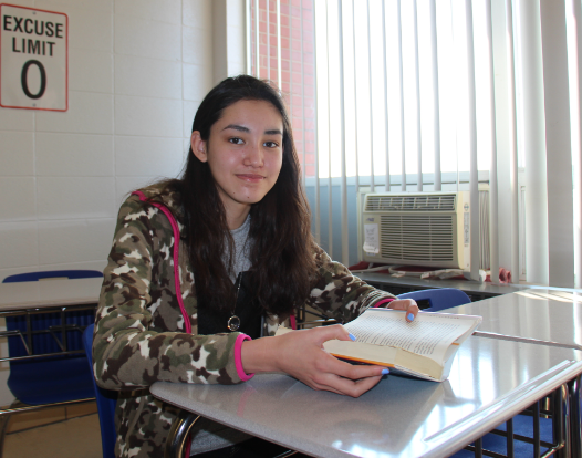 Freshman Kiara Macy smiles for the camera as she takes a break from reading in English- a new normal for the new GHS student who started at GHS in January, as English is her second language.
