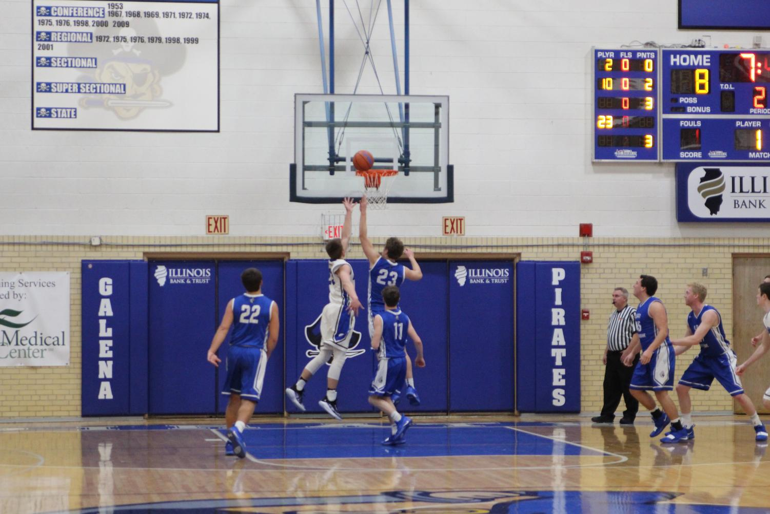 Senior- Cody Allendorf reaches to stop the East Dubuque # 23 to shooting for the basket.