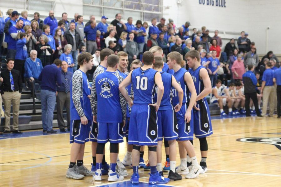 The varsity basketball team does a huddle before they start to discuss the game plan.