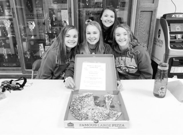 "Slices for Servant Leadership. Maddie Miller, Sami Wasmund, Olivia Kropp, and Mackenzie Muehleip, all class of 2020, sell slices of pizza in the morning before school. Many people, including teachers, purchase slices of pizza when they get to school in the morning. ""People get so excited when they walk in the door and there is pizza being sold,"" said Olivia Kropp. ""When people have early classes they enjoy being able to come get pizza before the actual school day starts!"""