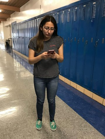 "Out of habit students like to take a quick look at their phones as they walk to class, to the bathroom, etc. Veronica Osorio '19 checks a message on her phone while in the hallway during class. With the new policy, Osorio would have gotten an automatic referral for simply checking a quick message. ""The day the teachers pay for my phone bill, is the day they can take away my phone. Give us back our phones, I miss her!!"" Osorio stated."