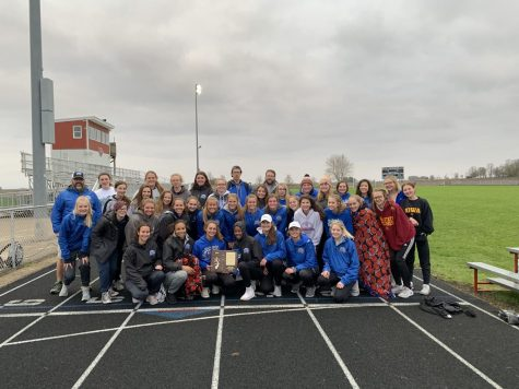 "Smiling for victory: The girls track team poses with their new 2019 Conference Champions plaque. The seniors gather in the front to show off their victory. ""I am thrilled that I got to end my senior season with another title"" said Wills '19."