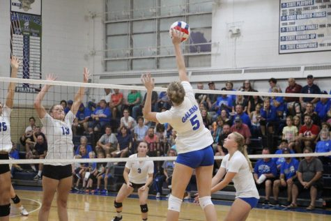 "McKenna Curran spikes the ball around the big Warrior block. The team McKenna was second in kills that night with a total of four. ""We had been working on seeing the block in practice earlier that week,"" said Curran. ""It was the perfect opportunity to use what I practiced."""