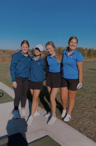 """Searching out the Competition.  Galena Girls patiently  waiting for their tee times to be called, pose for their final group picture of the season. In the picture, starting from left includes, Gracie Lange '21, Ava Miller '22, Julia Townsend '23, and Grace Hillard '22. """"Our team has a lot of potential and hopefully we can be back to back conference"""" said Hillard."""