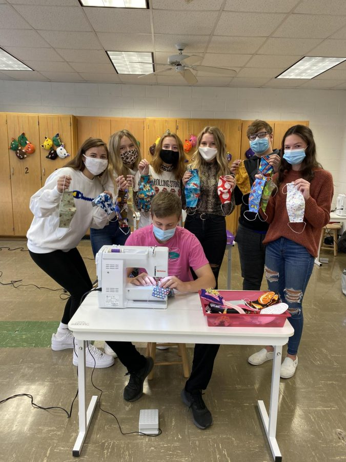 """All in making masks for the community, Danielle Stephanopoulos '23, Julia Townsend '23, Morgan McIntyre '21, Kate Moran '21, Alex Oberbroeckling '23, Maddy Glasgow '22, and Spencer Crawford '21 display the large selection of masks they created for the hospital. These students took on the task of making masks after Mrs. Bookless saw on Facebook that the Midwest Medical Center was asking for volunteers to donate. """"No volunteer work I have done in the past compares to this,"""" said Morgan McIntyre '21. """"Not only did we get to practice our sewing skills, but we get the satisfaction of knowing they are going to help others."""""""