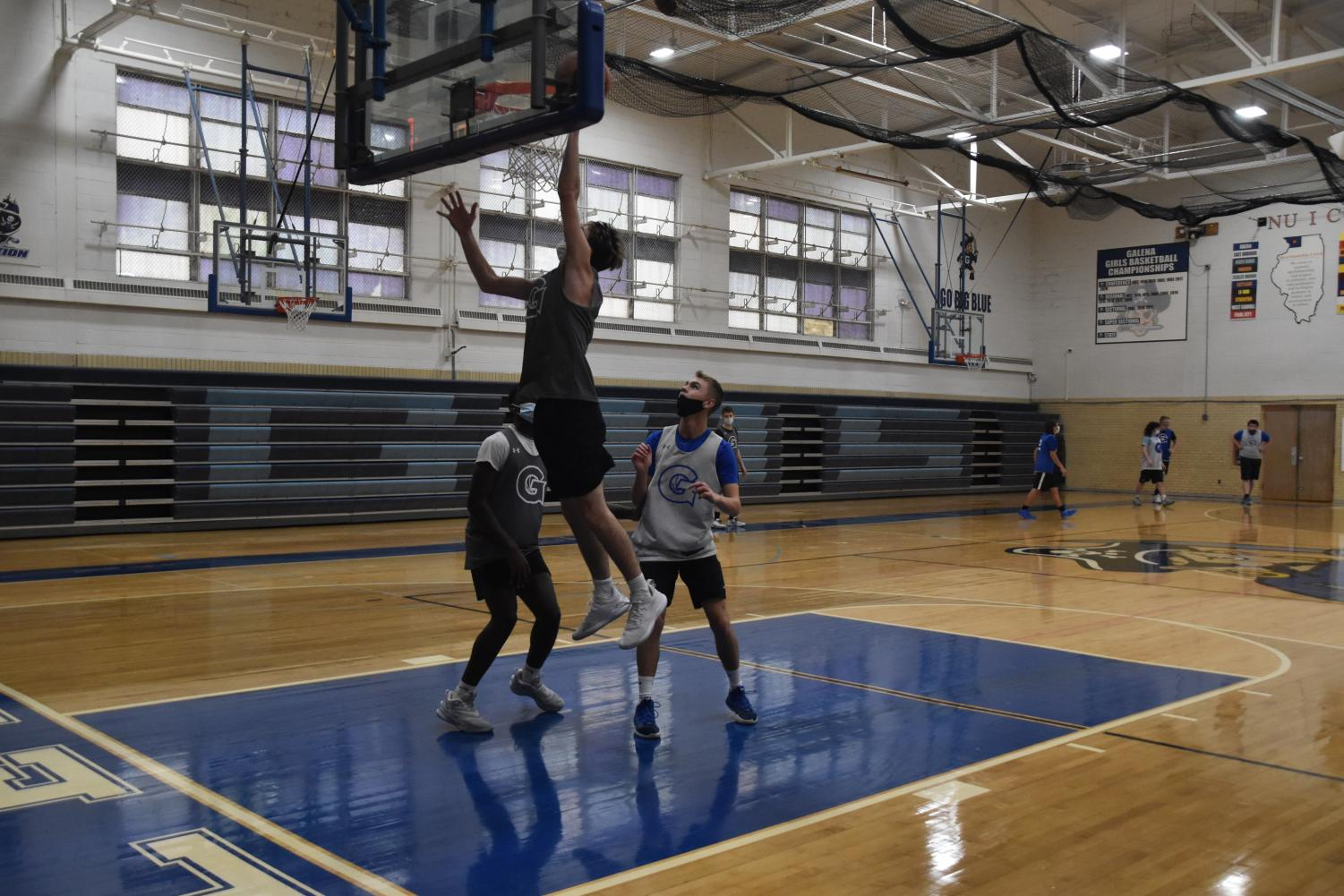"""Working and waiting for their time, Sam Hesselbacher '21 puts up a shot as Ryan Holland '21 and Khalid Newton '21 get ready for the rebound. GHS basketball teams have been practicing without games for a few months before they got the good news that they would be able to start competing again. The players have missed being able to actually compete against other teams. """"I just miss being able to compete with my teammates and playing in games,"""" said Ryan Holland '21. Thankfully, our teams are now back on the court playing the sport they love and GHS wishes them all the best of luck."""