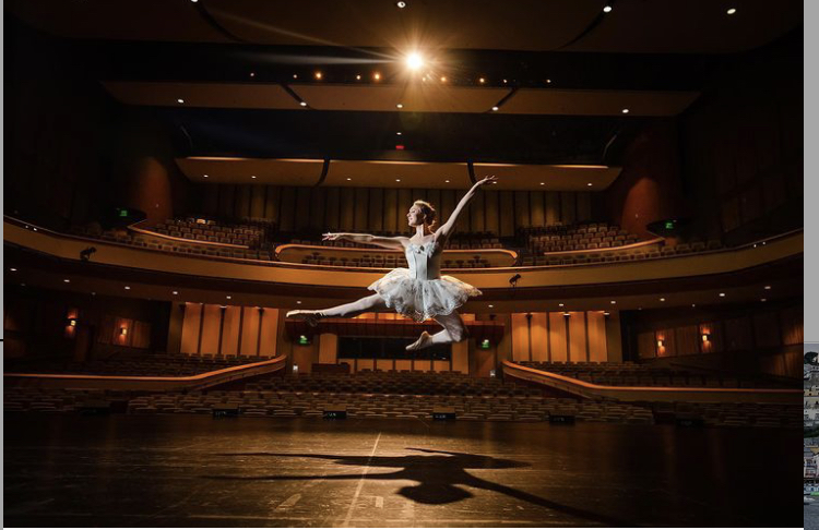 "Nicole Johnson does an Italian pas de chat across the stage with an empty house. Theaters are starting to open back up now so Johnson, and other dancers, will have a live audience again. ""There is nothing quite like performing in front of a live audience,"" explains Nicole. ""The support from the audience elevates the excitement and energy of the dancers."" Jenna and Nicole can't wait to perform for crowds again and hope that if you bought a ticket, you enjoy their production of Midsummer Night's Dream."