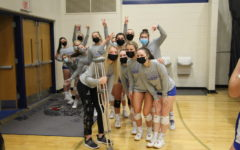 The varsity volleyball team poses for a picture before their game against River Ridge.