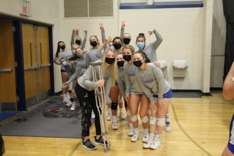 """The varsity volleyball team poses for a picture before their game against River Ridge."""